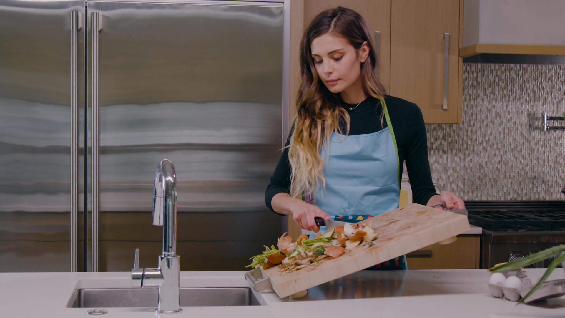 A woman brushing food from a cutting board into her sink.