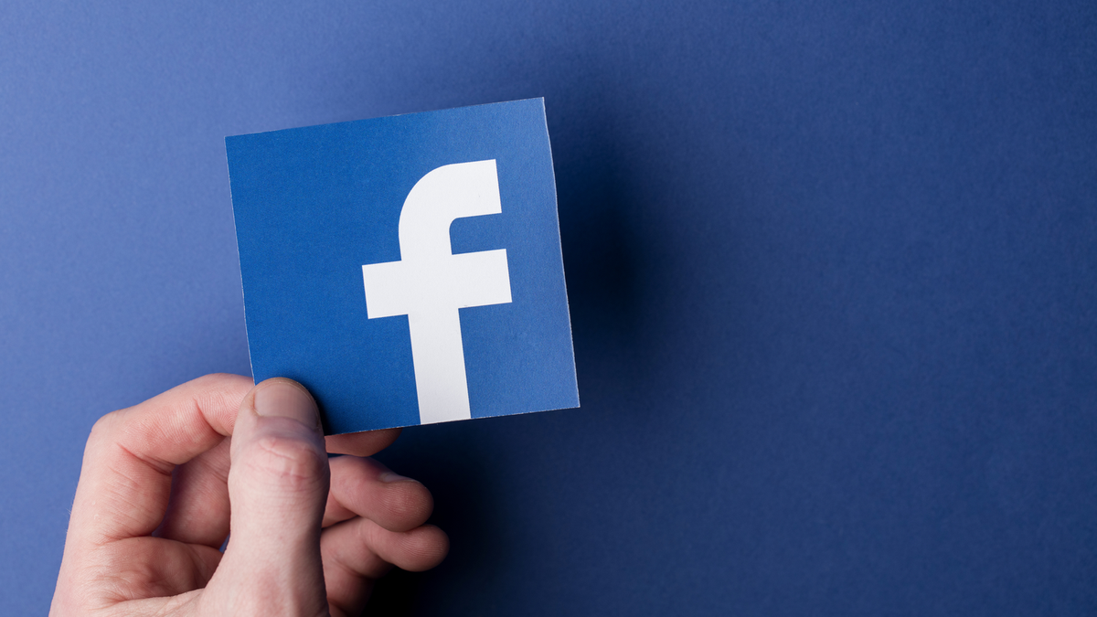 A paper cutout of the Facebook logo being held in front of a Blue background
