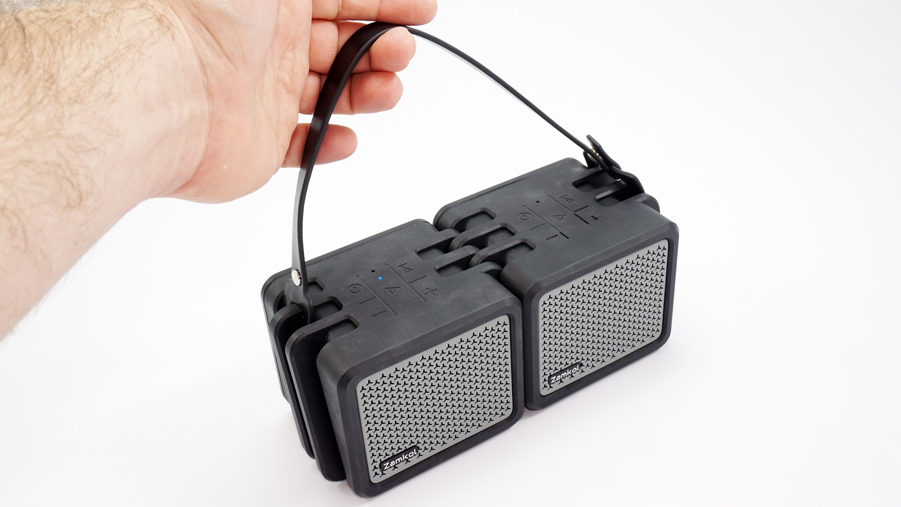 A hand holding the Zamkol speakers by the faux leather strap.