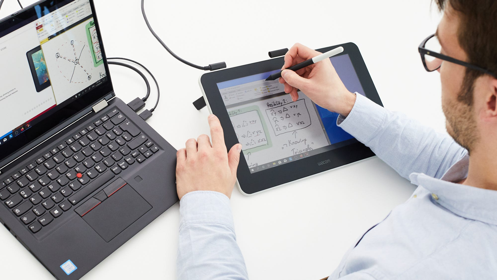 A man writing match equatons Wacom One Pen Display Tablet attached to his tablet.