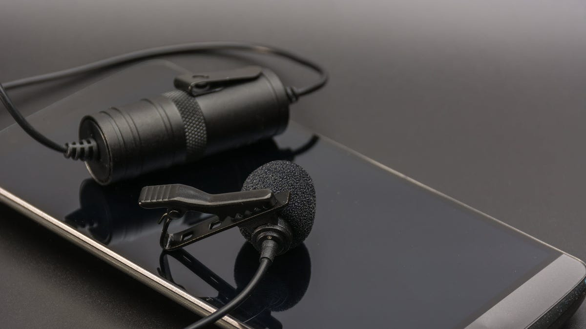 A lapel mic resting on a smartphone.