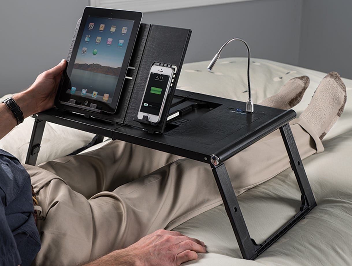 The Sharper Image Laptop and Tablet Tray on a bed, with a man's outstretched legs underneath, his hand resting on a tablet on the tray.