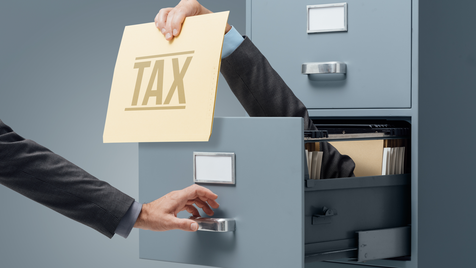 Businessman inside a filing cabinet giving a tax file to an office clerk