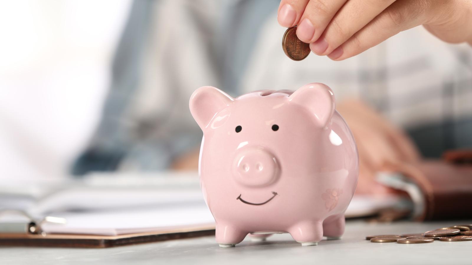 A woman putting money into a piggy bank