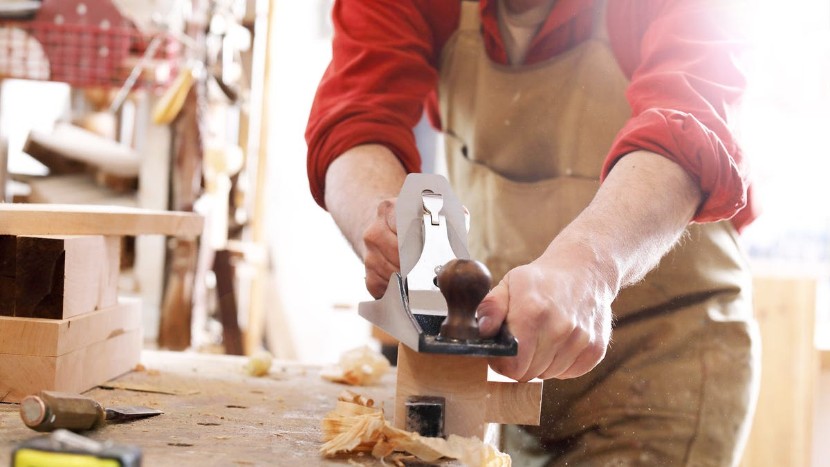 A man, planing a long oak board with a hand plane.