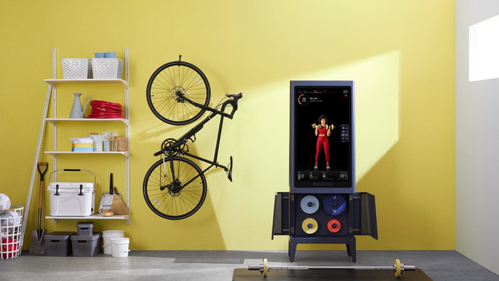 The Tempo Studio in a garage with an open cabinet showing weight plates.