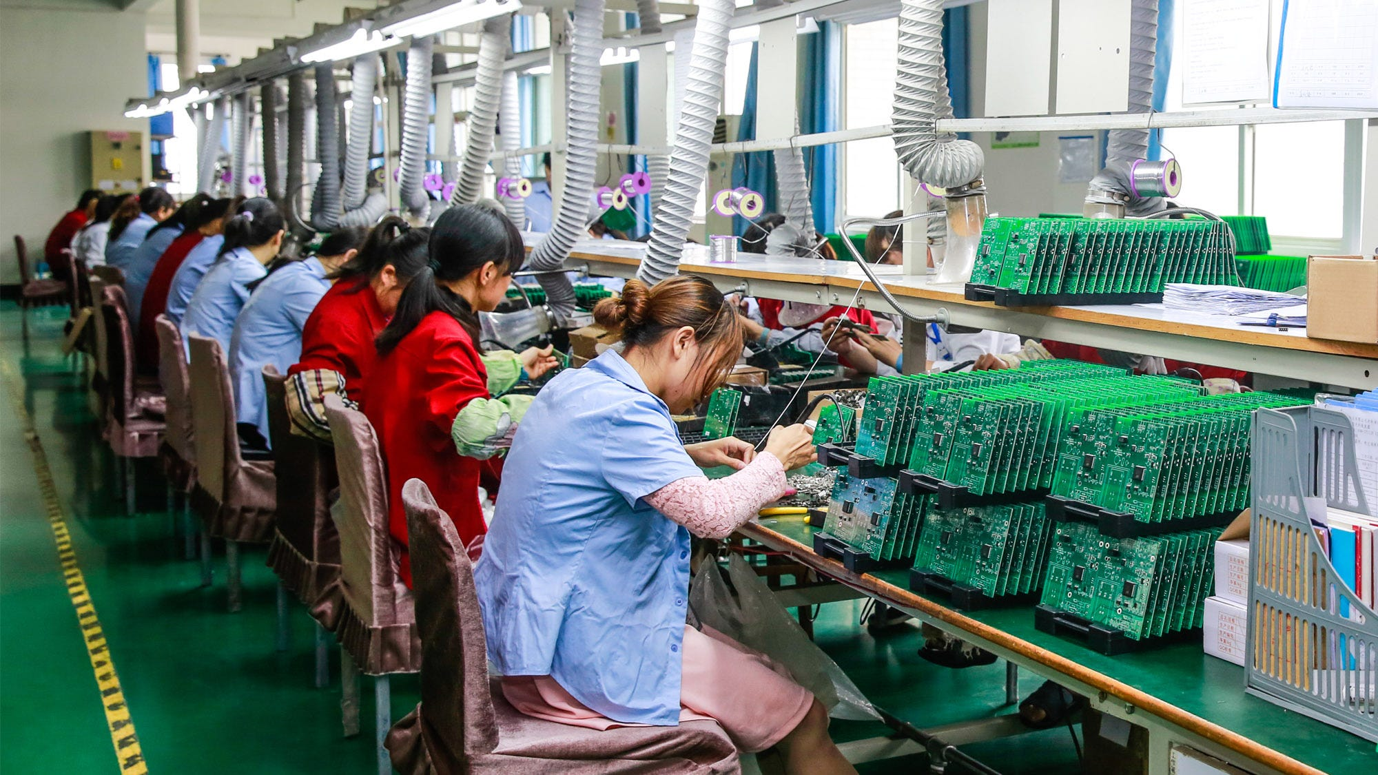 Factory workers in Jiangxi manufacture circuit boards in an assembly line.