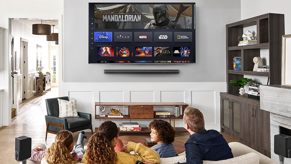 A family watching Disney+ on a Vizio TV in a living room.