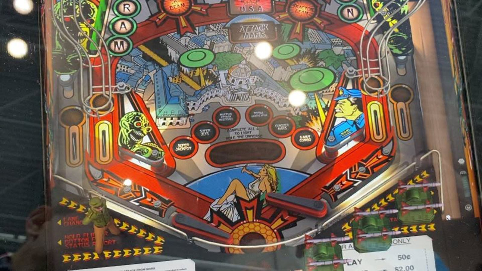 A closeup of a pinball playfield, showing bumpers and scoring options.
