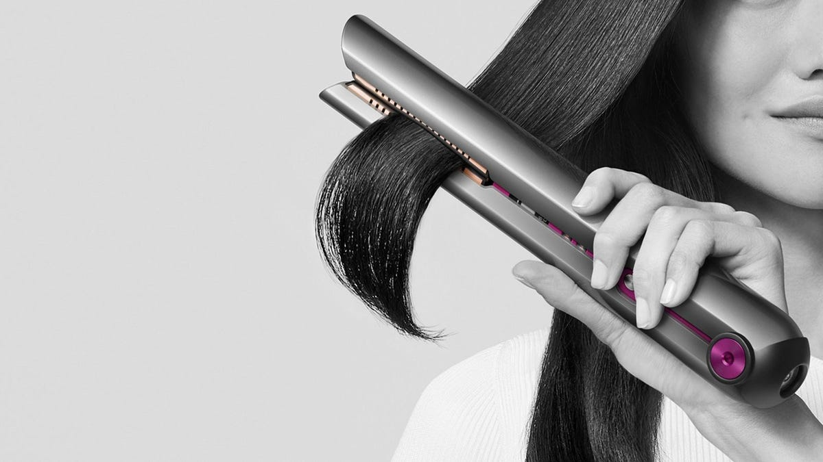 A woman using the new Dyson Corrale hair straightener
