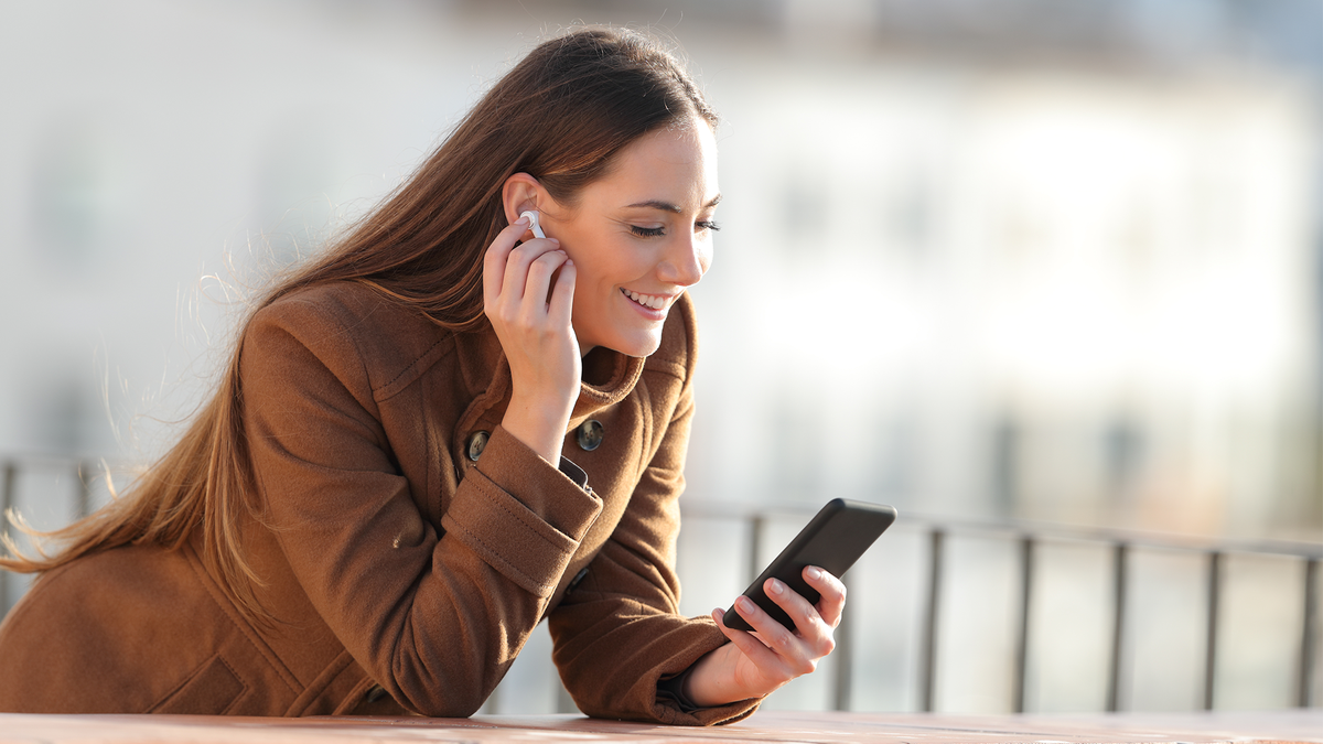 A woman listens to podcasts on her Android phone.