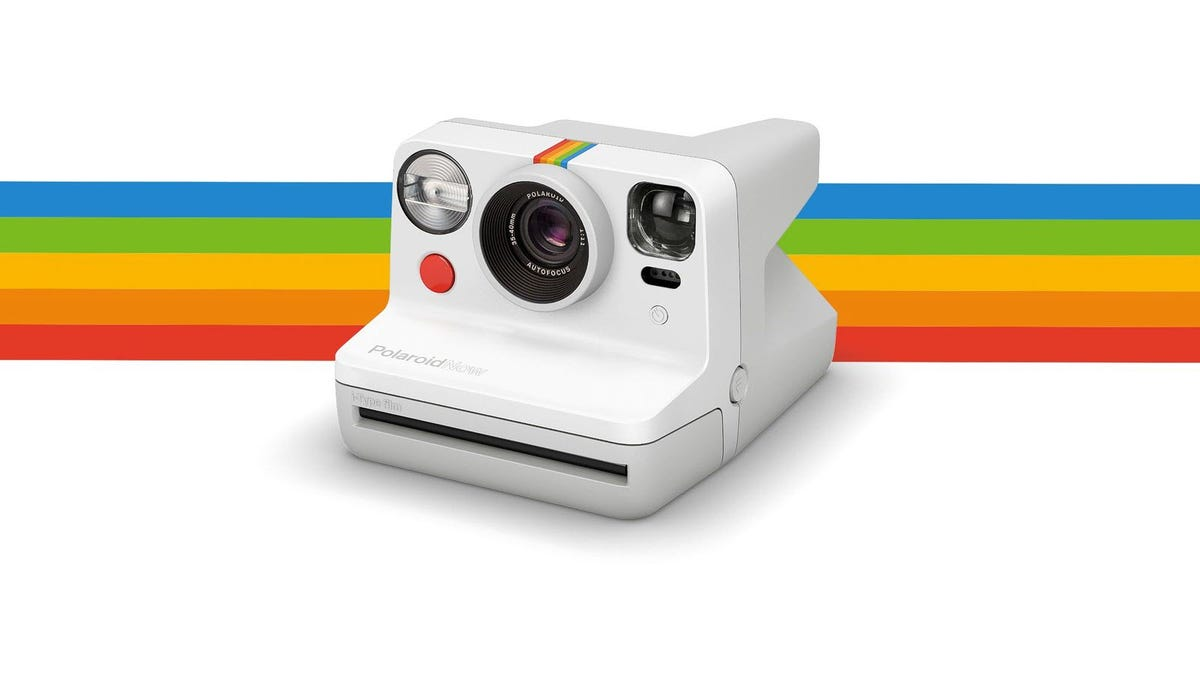 A white Polaroid camera against a rainbrow striped backdrop.