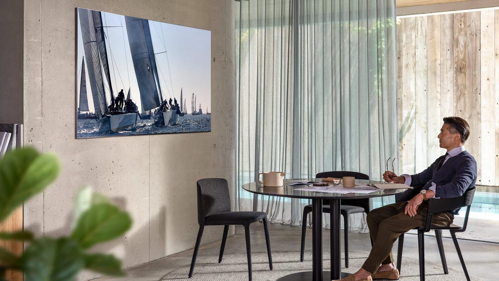 A man watching a bezelless TV mounted on a wall.