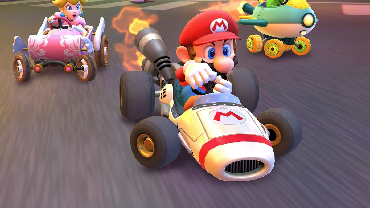 Mario in a race cart just ahead of Princess Peach in a pink race kart