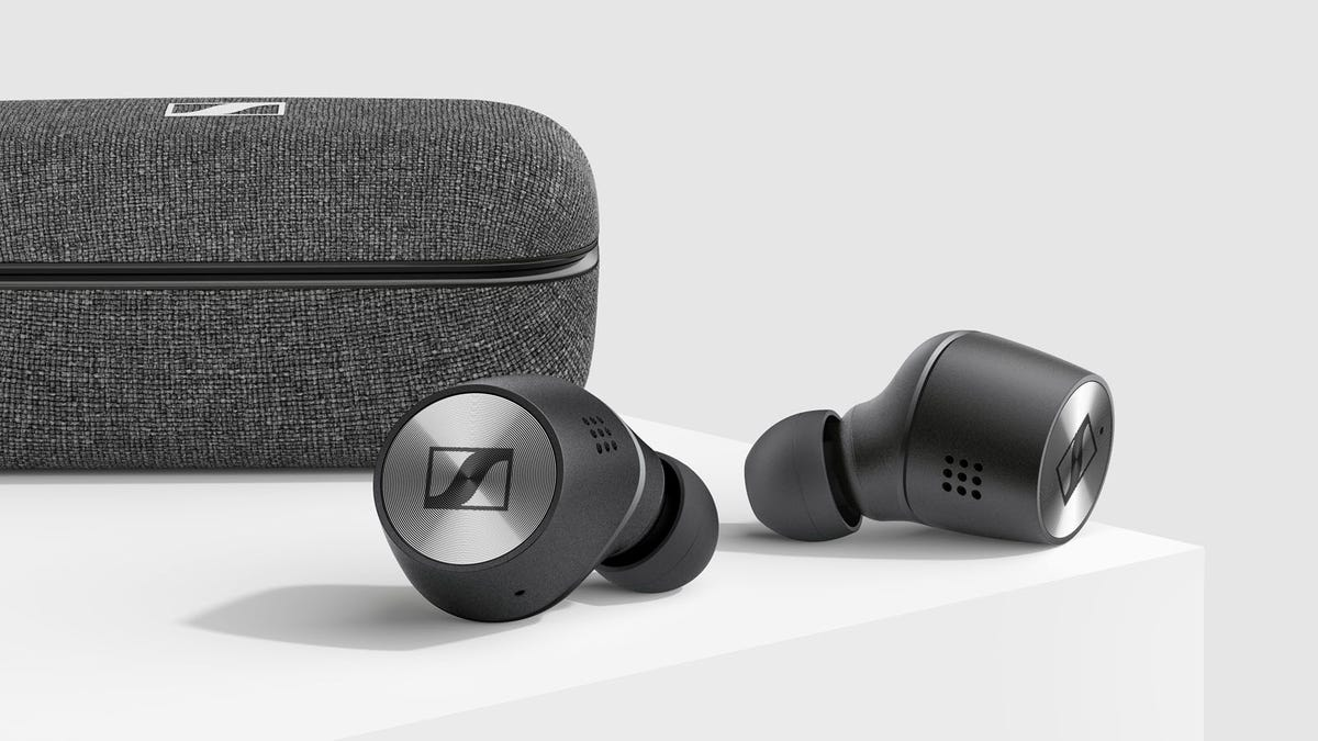 A pair of grey Sennheiser Momentum True Wireless earbuds next to a grey fabric case.