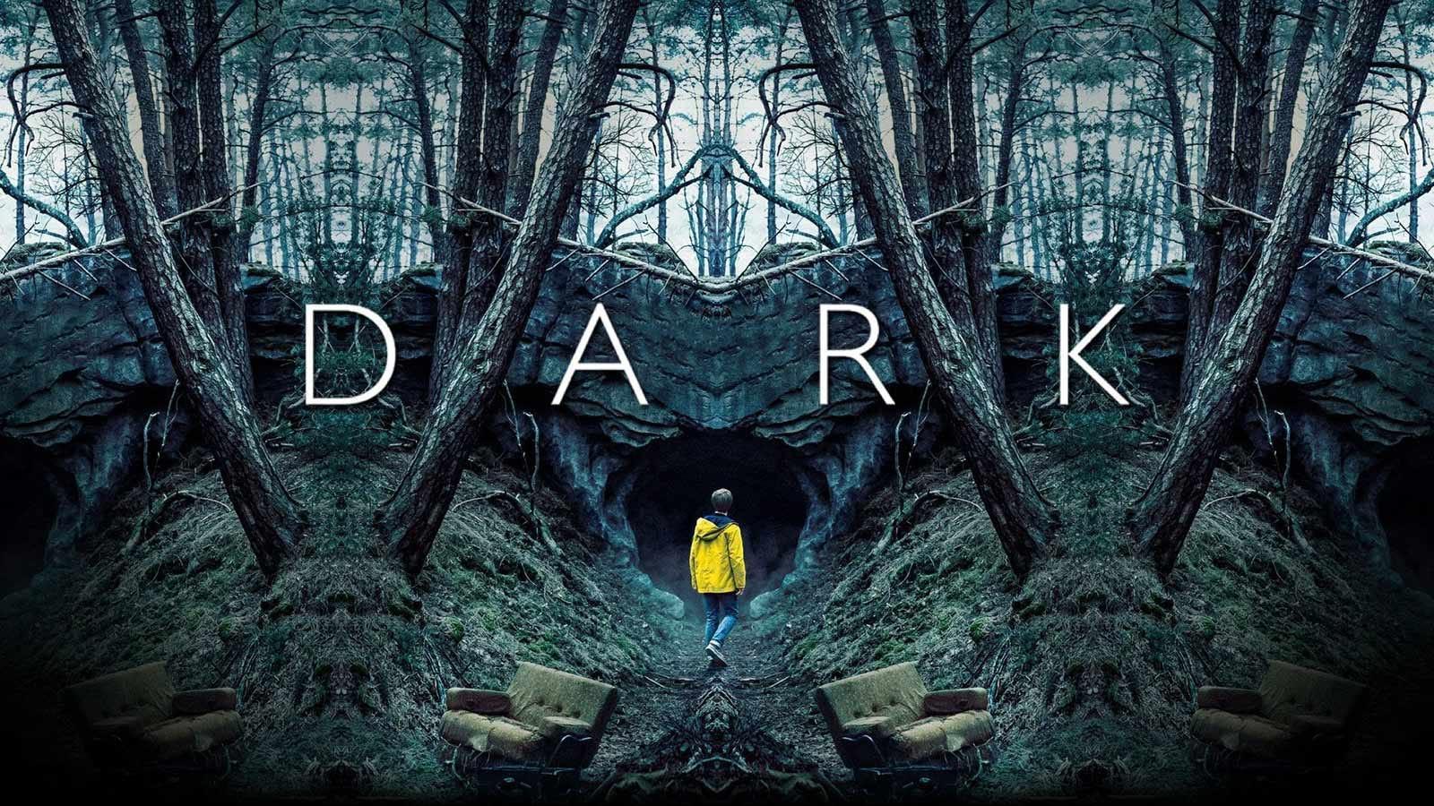 A boy in a yellow rain slicker walks towards an eerie cave opening.
