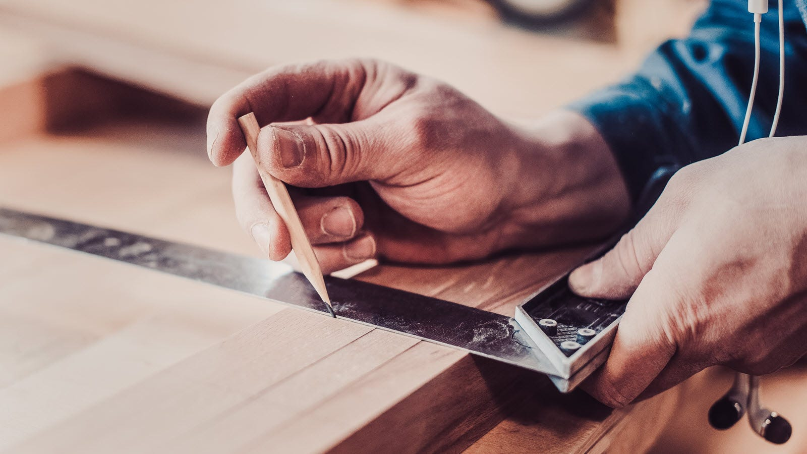 A man drawing a layout line on lumber using a square and a pencil
