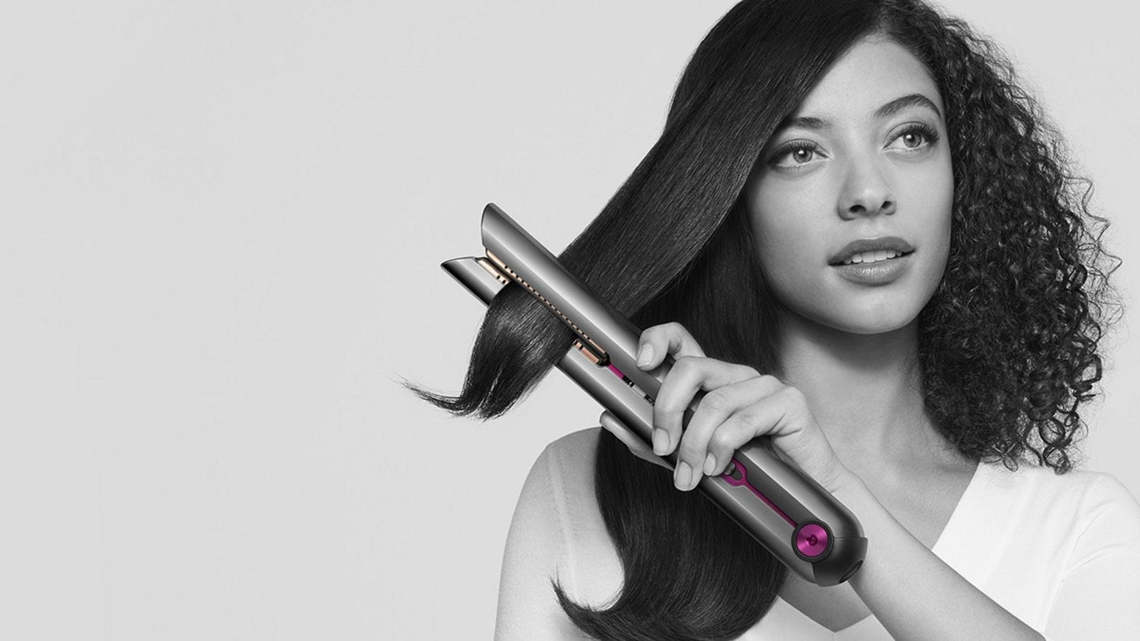 A woman using the Dyson Coralle hair straightener on one side, with curly hair on the other
