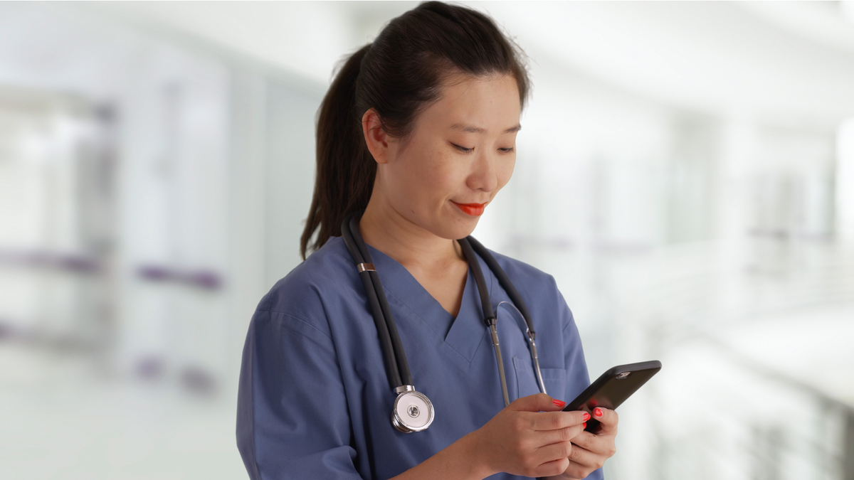 A doctor looking at her smartphone.