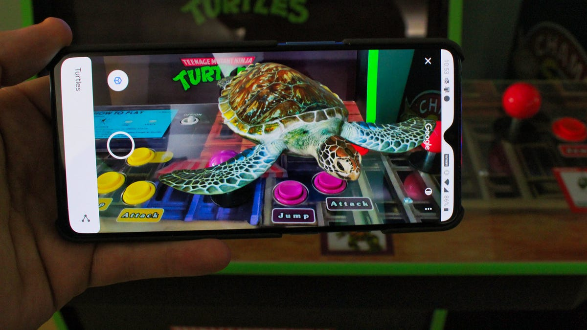 A 3D turtule on a phone held over a TMNT arcade