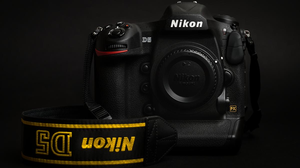 A Nikon D5 camera in a dark room.