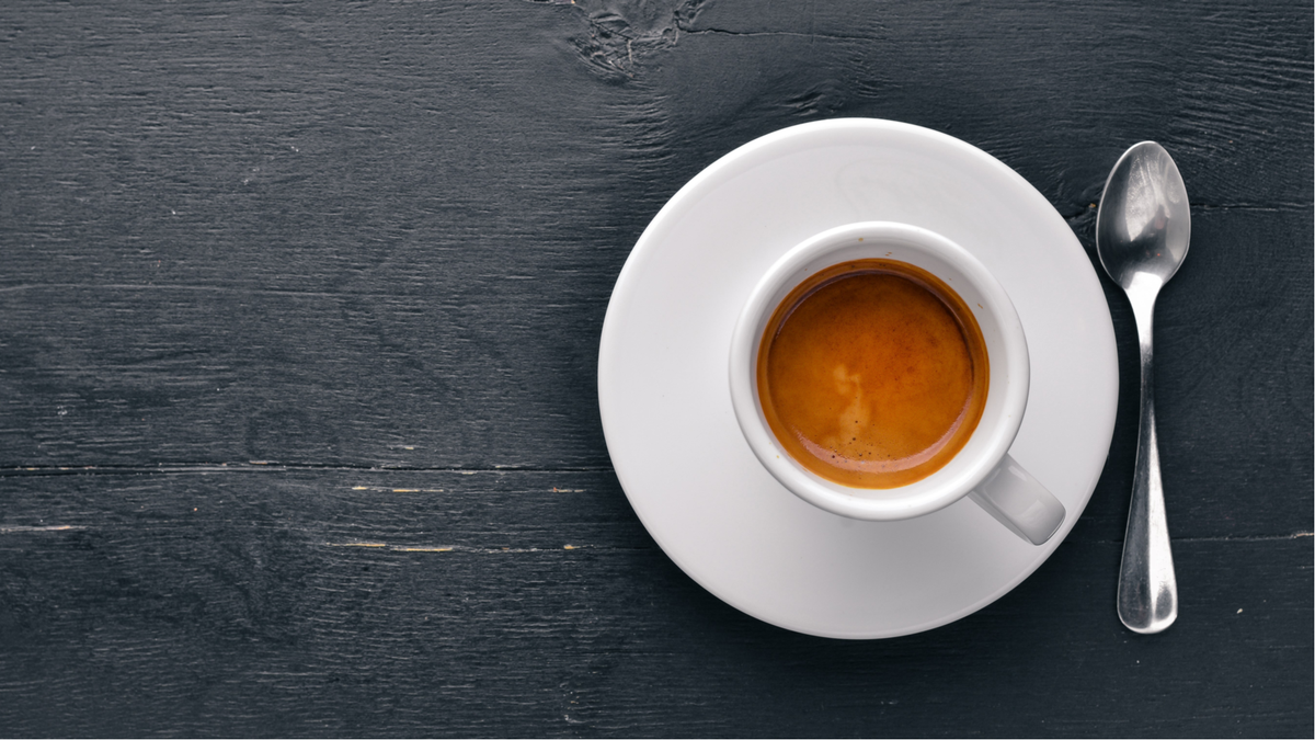 A cup of espresso on a black table