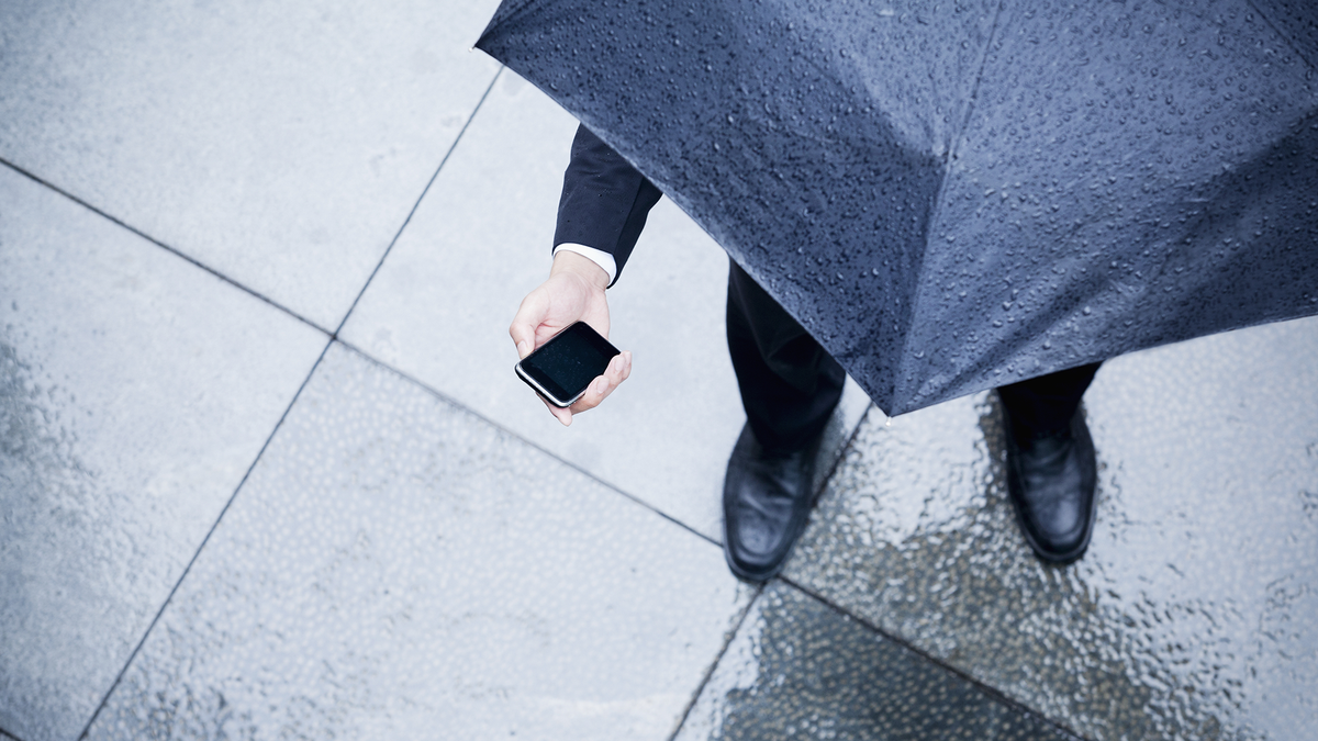 A man checks his phone in the rain.
