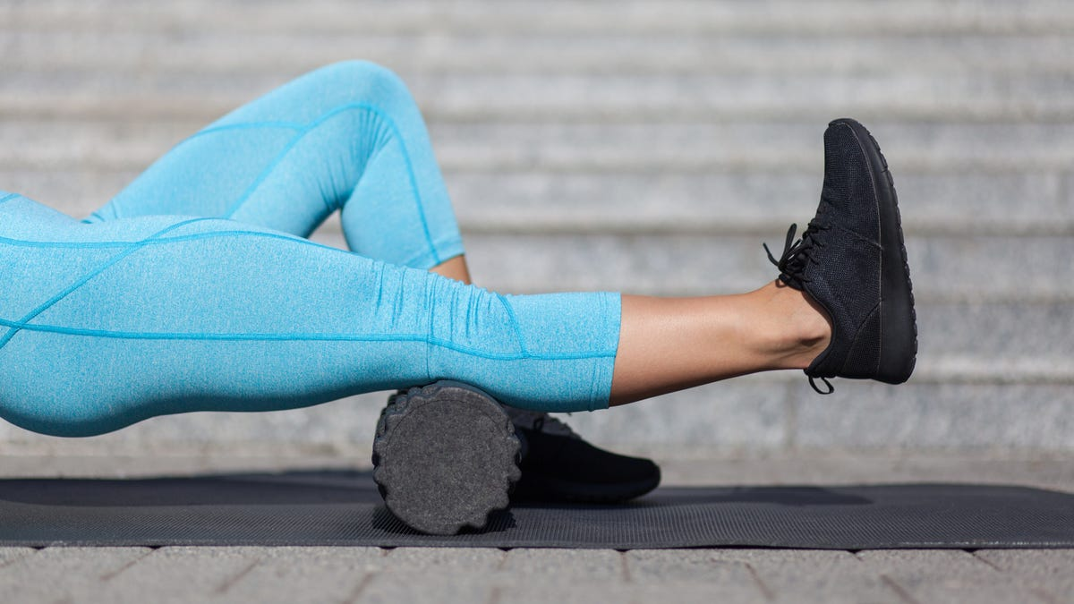 A woman using a foam roller on her calf muscle