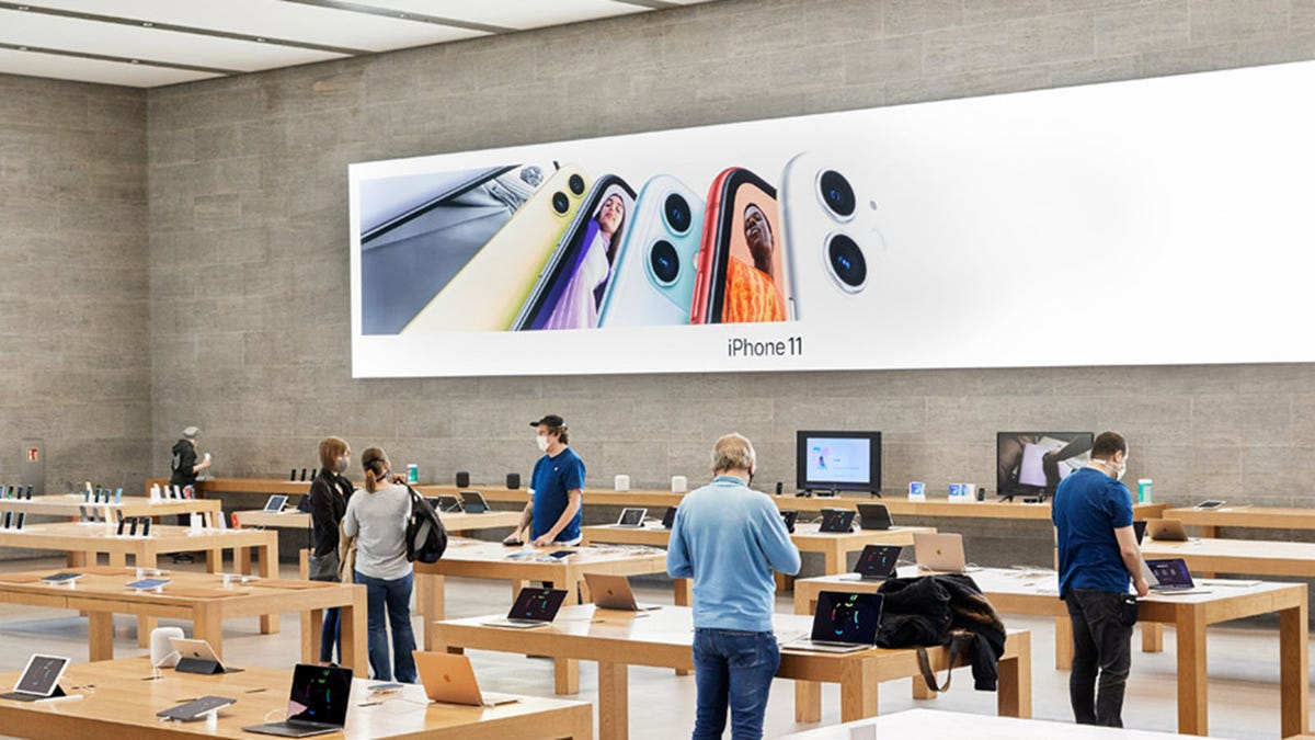 An sparsly populated Apple Store, with customers and employees wearing masks.