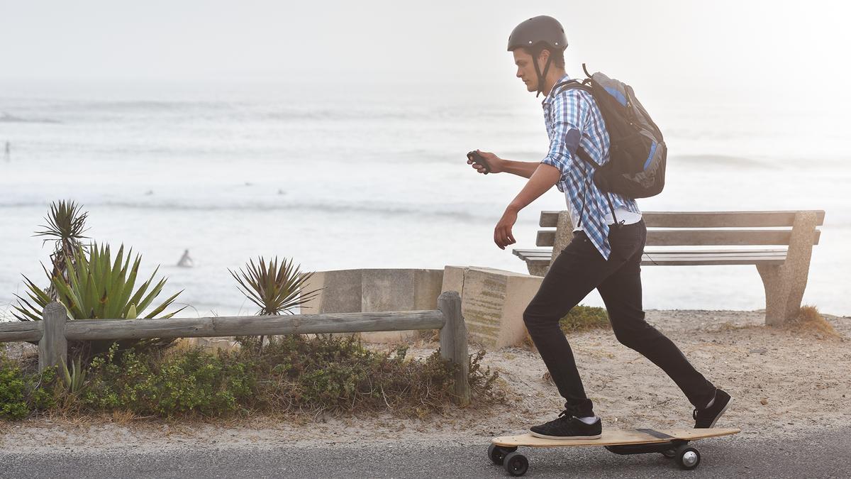 A man riding on an electric skateboard.