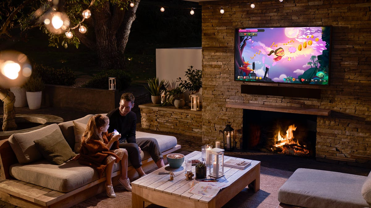 A man and his daughter watching TV outdoors on a patio.