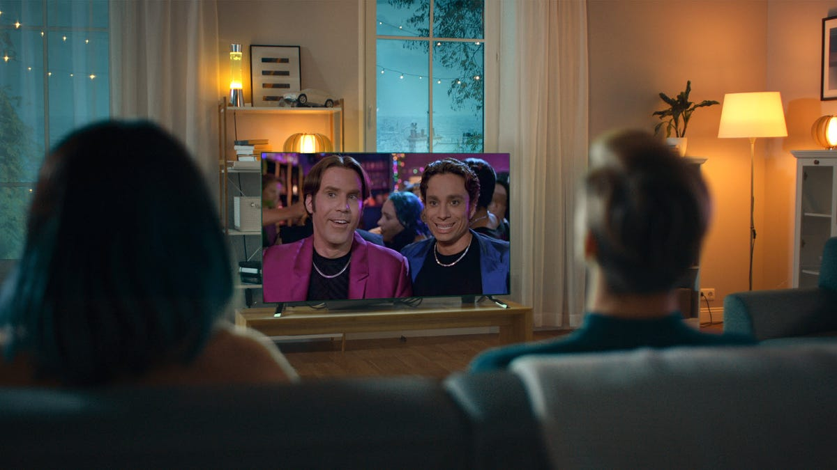 Two people watching 'A Night at the Roxbury' on a TV.