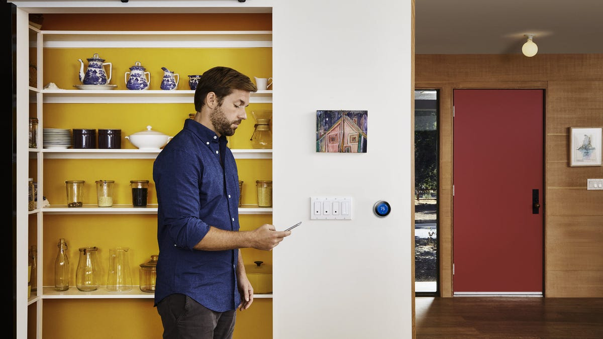 A man walking by four Wemo smart light switches.