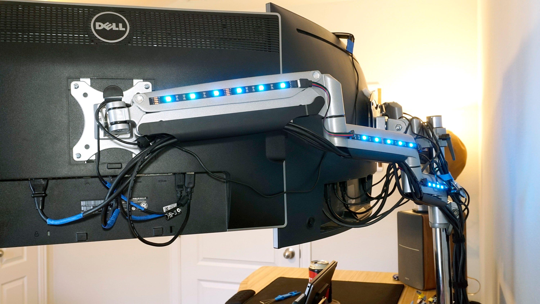 Behind the monitors.