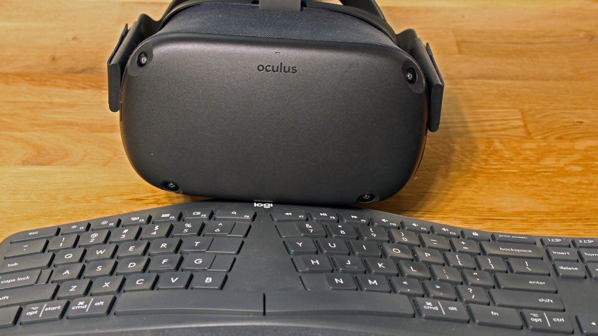 An Oculus Quest in front of a Logitech ergonomic keyboard.