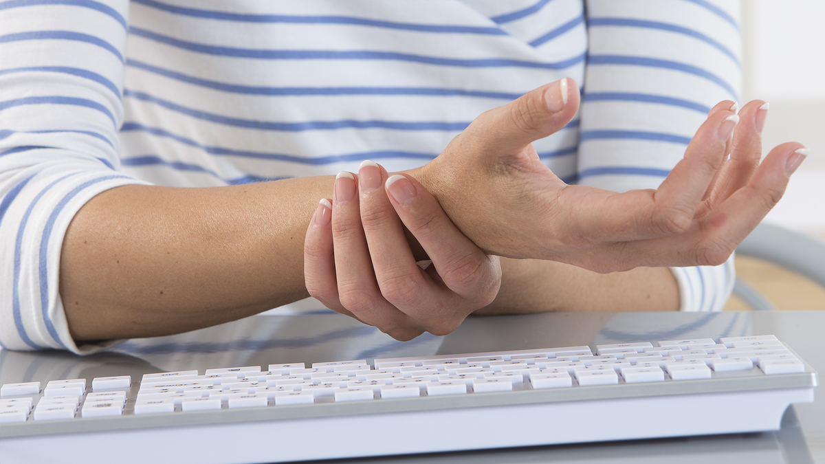 A woman experiencing wrist pain while typing.