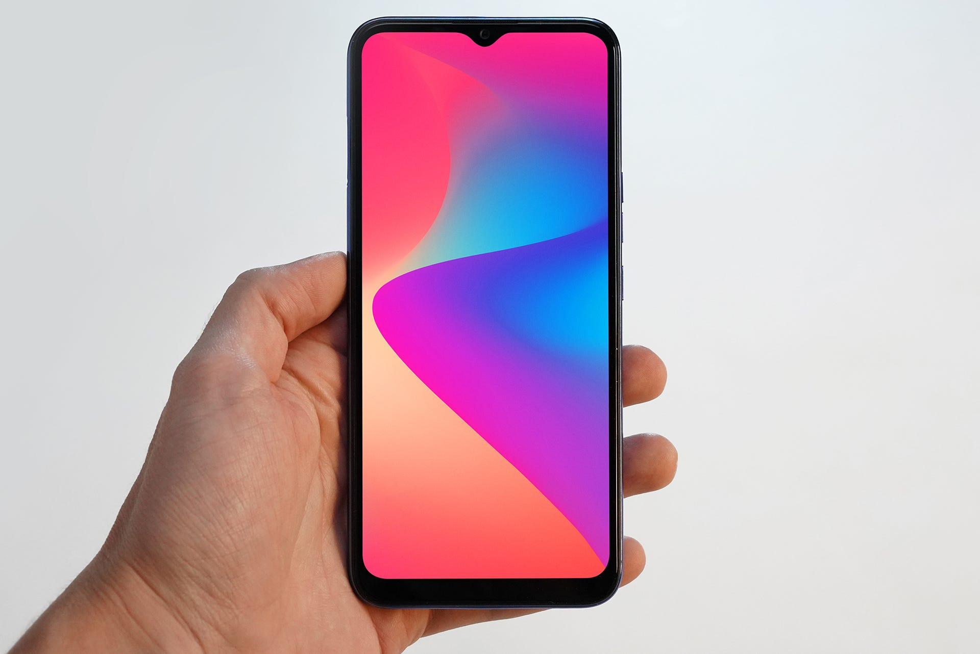 Blu G90 phone, in hand with colorful screen