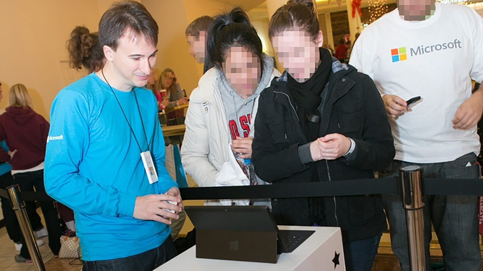 The author, standing next to two people looking at a Surface RT.