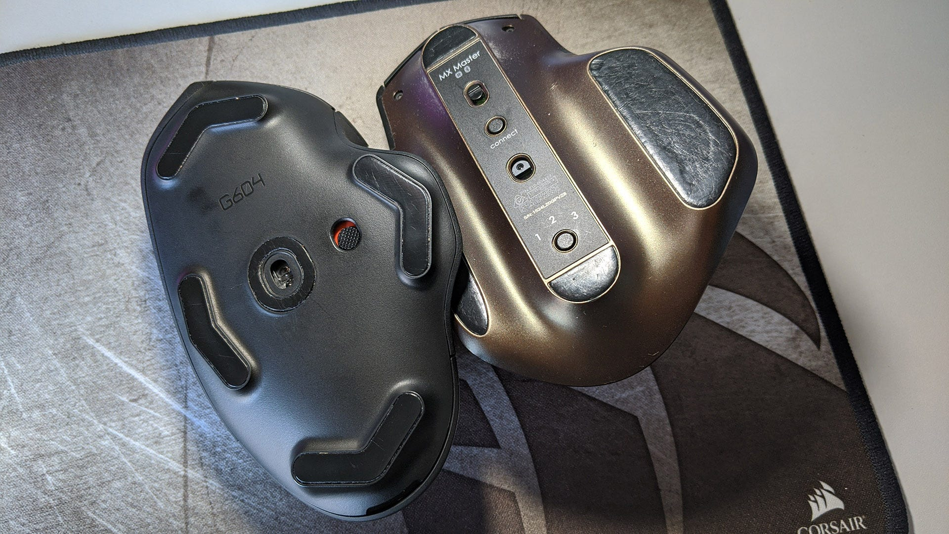 Two computer mice, upside down, with one worn and one clean.