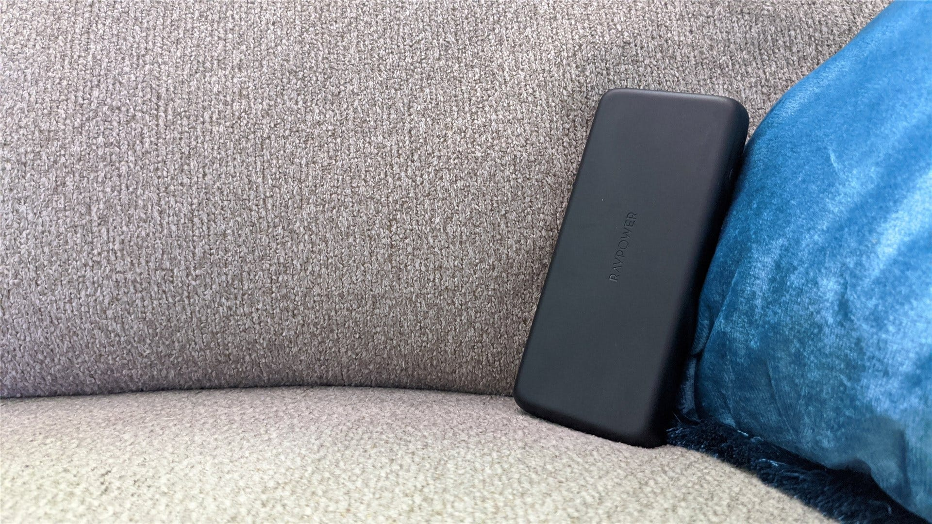 A RavPower battery on a tan couch with a teal pillow
