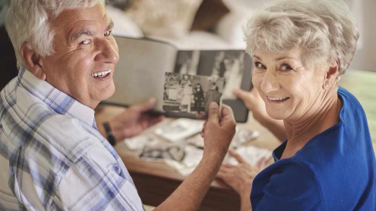 Elderly couple looking through photo book at pictures of relatives
