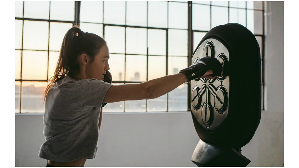 Liteboxer digital rhythmic boxing trainer being hit by a female athlete