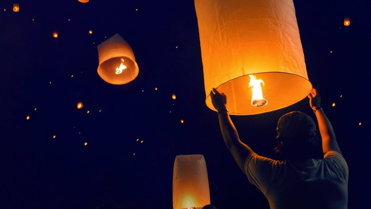 A person letting go of a flying paper lantern.