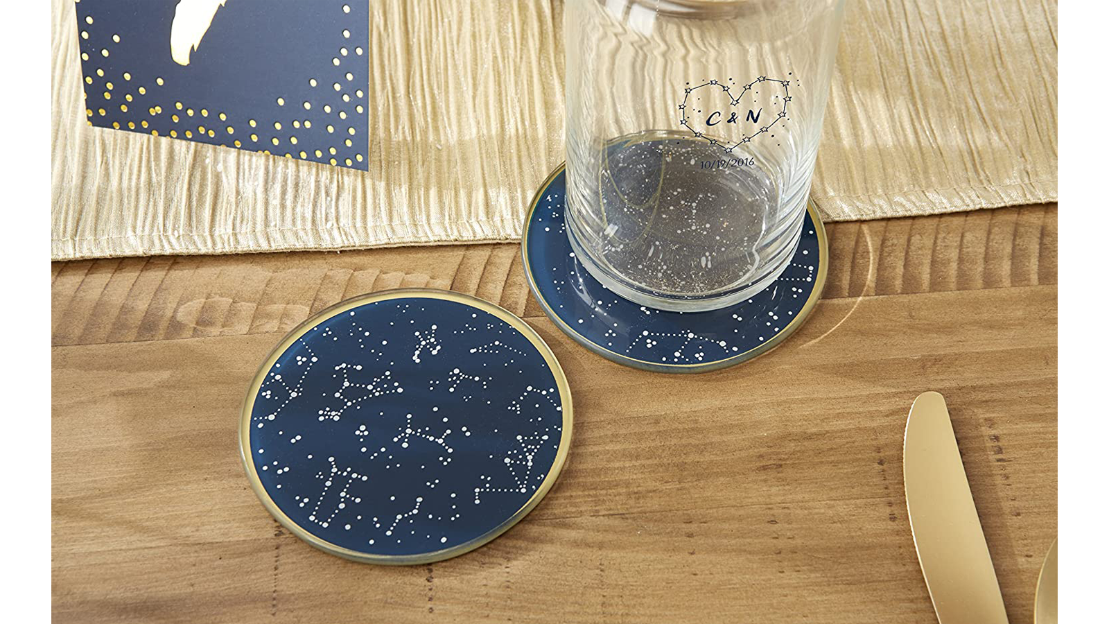 Gold, white, and navy blue coasters with gold rim set on table with a cup