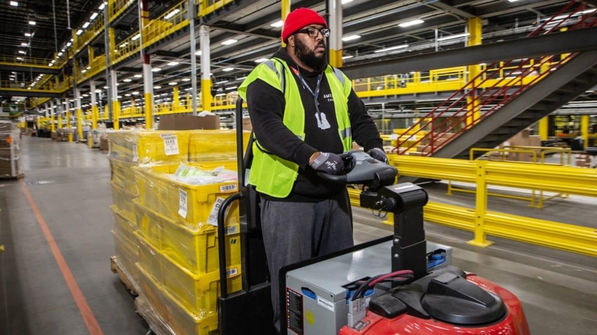Amazon factory worker rides an indoor hauling cart