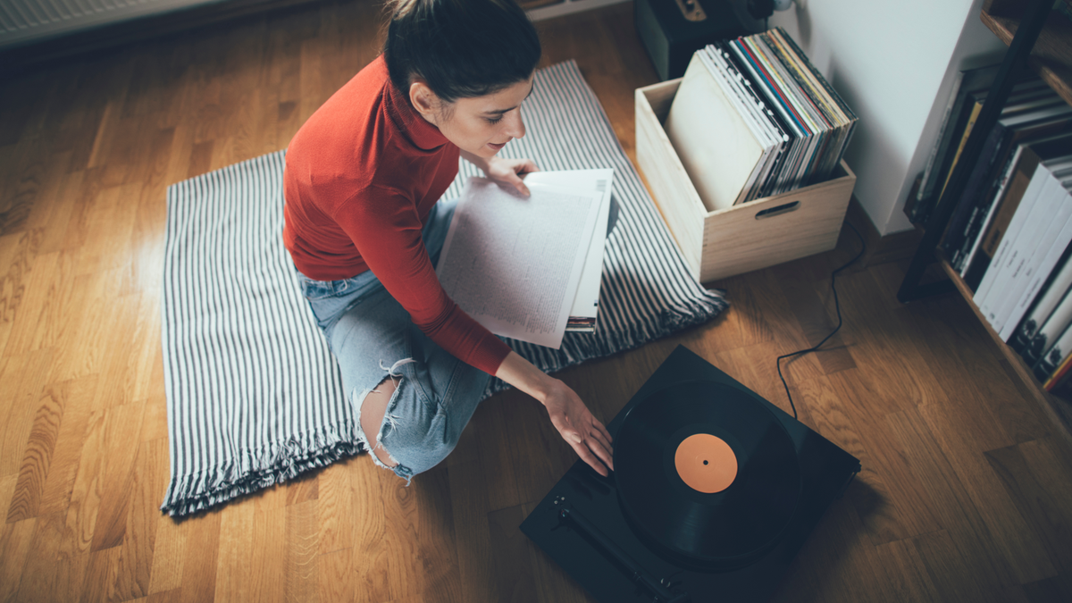 Young audiophile playing vinyl record on turntable in her home