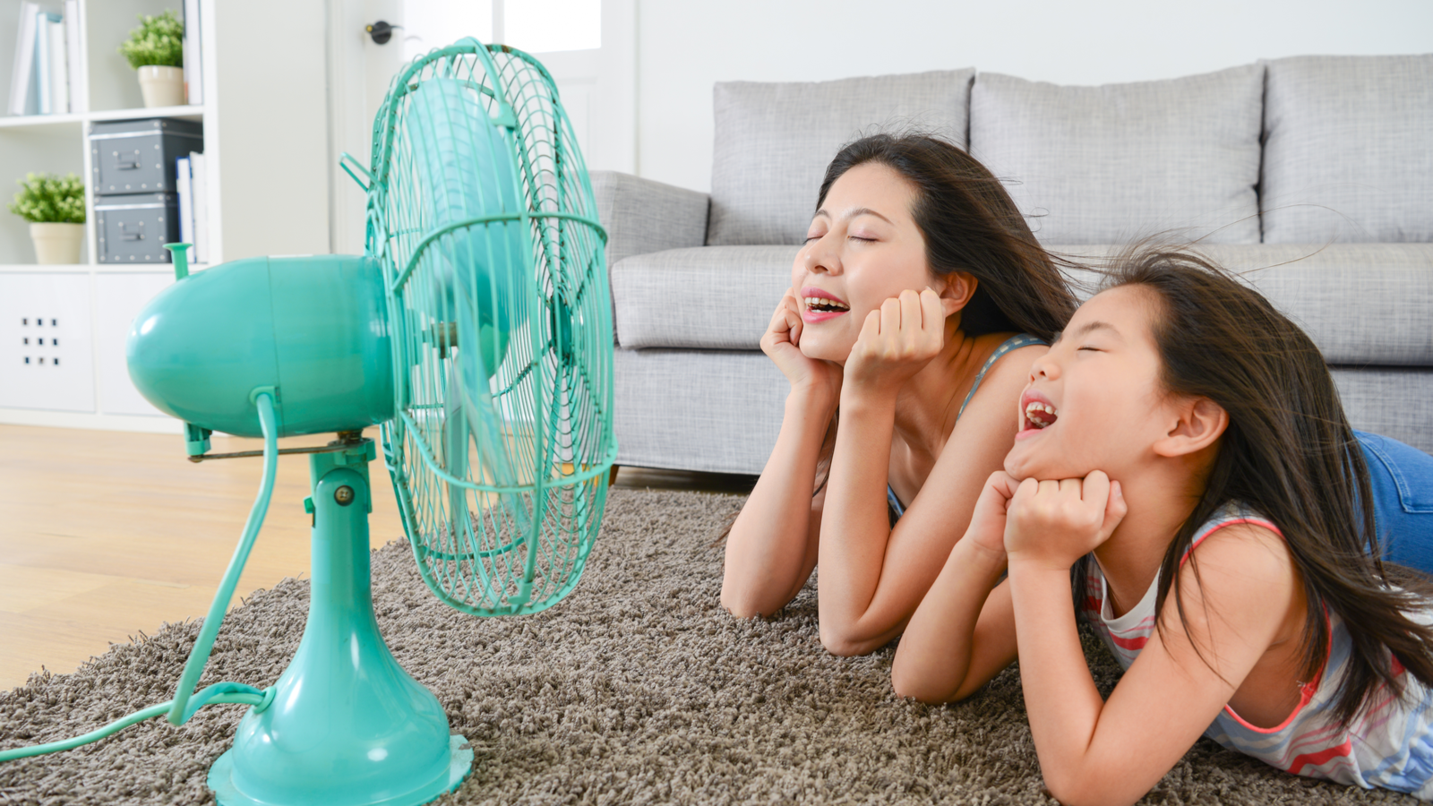 pleasant mother with young daughter lying down in living room floor and facing an electric fan enjoying blowing cool wind together during summer