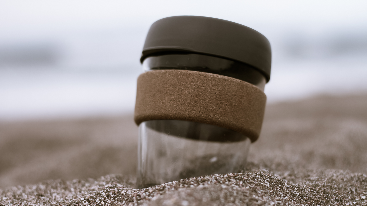 A reusable coffee cup in sand