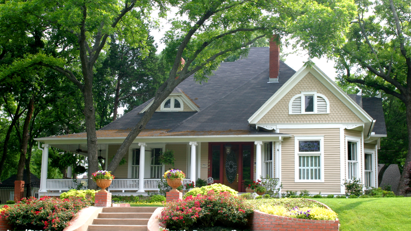 extremely colorful classic restored house in rural city with trees and covered porch