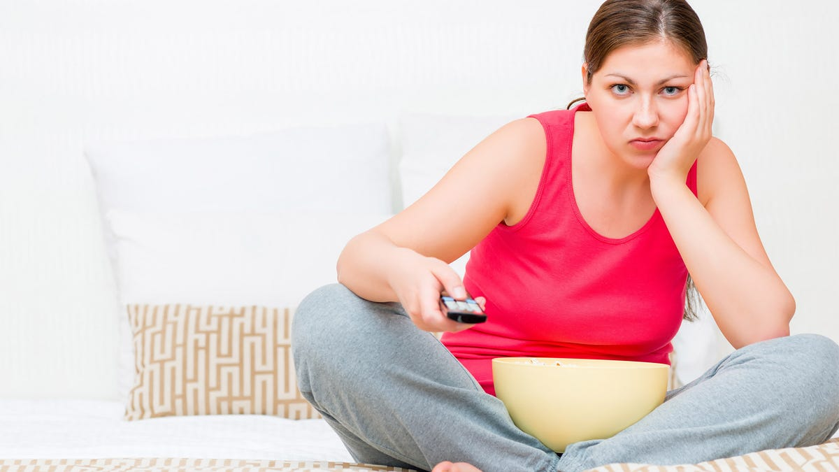 Annoyed woman watching TV with remote
